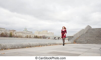 Young girl in a red dress is walking along the promenade