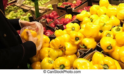Young girl in a supermarket chooses a juicy, fresh yellow peppers and puts it in a package close up.