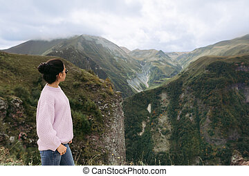 young girl in a sweater is looking at the Caucasian mountains