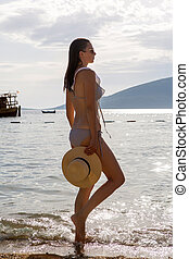 young girl in a swimsuit standing on the beach at sunset