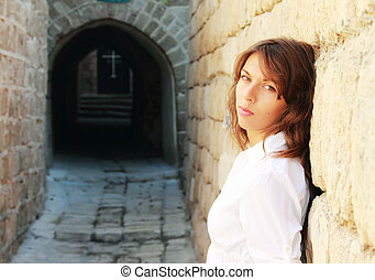 young girl in a white shirt is standing against a stone wall. In the distance can be seen the cross of the church.