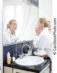 Young girl in bathrobe looks at the mirror in bathroom