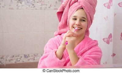 Young girl in bathrobe playing with teethbrush - Young girl...