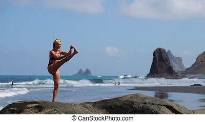 Young girl in bikini balancing standing on one leg doing...