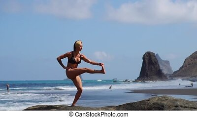 Young girl in bikini balancing standing on one leg doing yoga standing on a rock by the ocean on a black sand beach