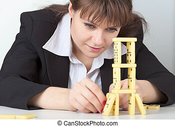 Young girl in black concentrated builds tower of dominoes - ...