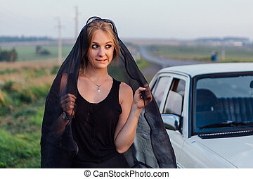 Young girl in black dress near retro car at sunset