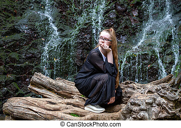 Young girl in black posing squatting on a large dry tree against the background of a mountain waterfall