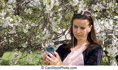 Young girl in blooming trees takes a selfie