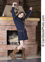 young girl in blue jersey near fireplace