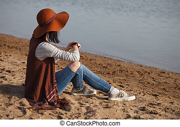 Young girl in boho style clothes using smart wrist watches