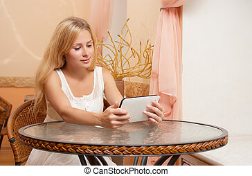 Young girl in cafe with tablet