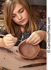 Pretty young girl making bowl in clay studio