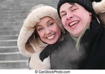 young girl in coat with hood embracing man from back and laughing, half body, winter day, stairs on background