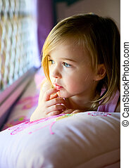 Young Girl in contemplation on her bed looking out her bedroom w