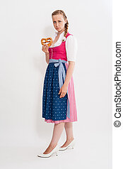 Young girl in Dirndl with pretzel in his hand