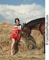 young girl in dress with horse near hay