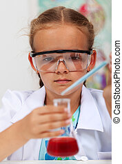 Young girl in elementary science class with chemical recipient and pipette