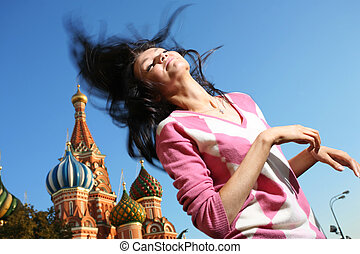 Young girl in euphoria waves her long hair over blue sky at Red Square, Moscow, Russia. Saint Basil's Cathedral behind.