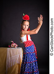 Young girl in flamenco outfit clapping hands