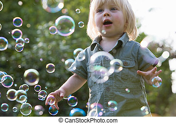 Young Girl In Garden Chasing Bubbles