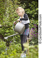 young girl in garden watering the plants