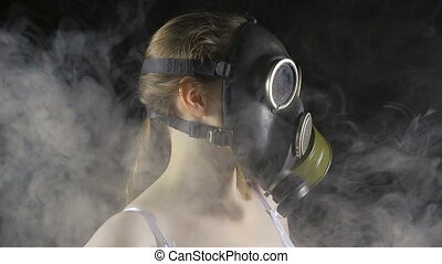 Young girl in gas mask among smoke