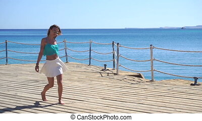 young girl in glasses and a skirt day runs on the beach in slow motion