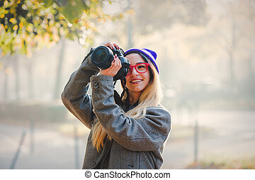 Young girl in glasses and hat with camera