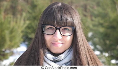 Young girl In glasses looking at the camera and smiling. Portrait of beautiful woman. Winter background. Slow motion Close up