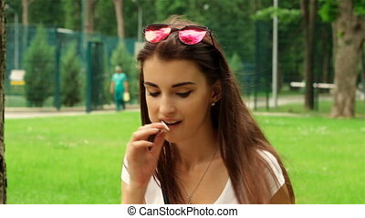young girl in glasses on her head sits in the Park and sucks lollipop
