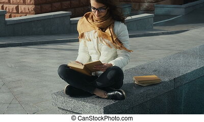 young girl in glasses reading a book