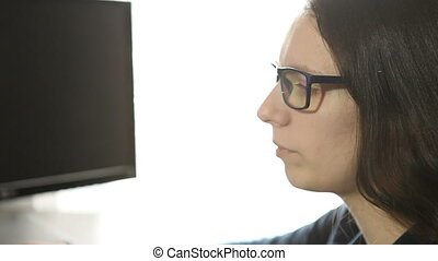 young girl in glasses sitting at a computer works