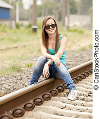Young girl in glasses sitting at railway.
