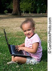 Young Girl in Green Grass with Laptop Computer