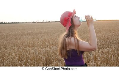 Young girl in hat holds a bottle of water in hand and drinks...