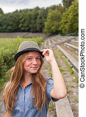 Young girl in hat outdoors.