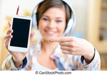 Young girl in headphones showing her smartphone.