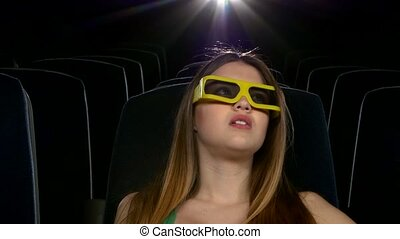 young girl in horror film 3D at the cinema. eating popcorn. Close up