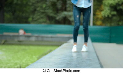 girl in jeans climbed up on the curb and goes near water -...