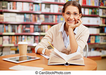Young girl in library - Portrait of clever student looking...