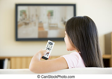 Young girl in living room with flat screen television and remote