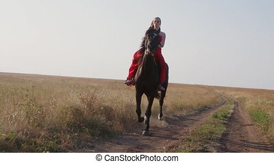 Young girl in long red dress riding black horse on dirt road across a field
