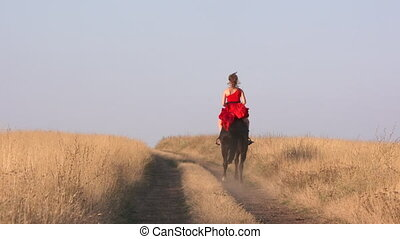 Young girl in long red dress riding black horse on dry grassland