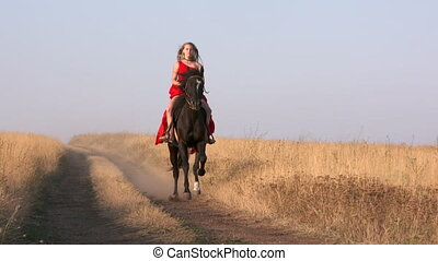 Young girl in long red dress riding black horse on path across dry grassland. Beautiful female rider rides galloping stallion in slow motion. Girl's bright gown blowing in the wind.
