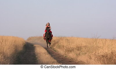 Young girl in long red dress riding black horse on path across dry grassland