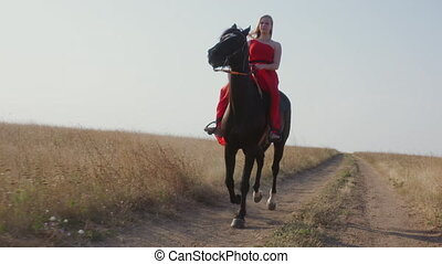 Young girl in long red dress riding black horse across a field in slow motion