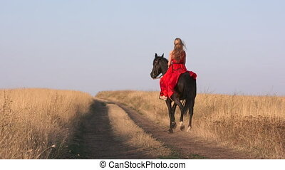 Young girl in long red dress riding black horse on dry...
