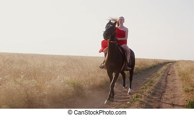 Young girl in long scarlet red dress riding black horse on dry grassland