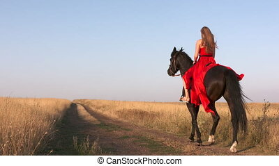 Young girl in long scarlet red dress riding black horse...